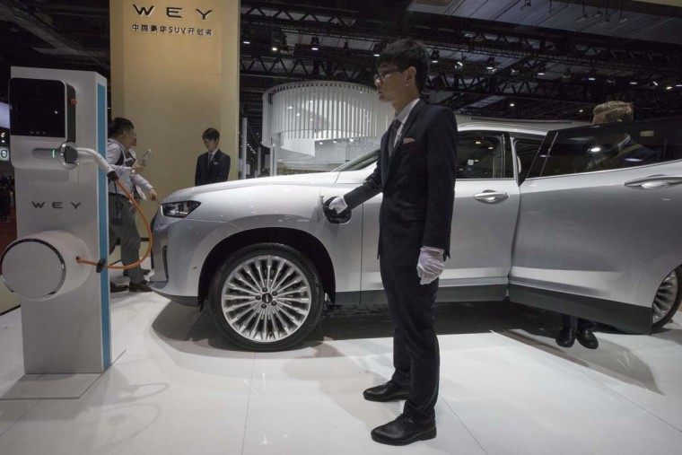 A worker stands near a electric SUV displayed from Chinese auto brand WEY during the Auto Shanghai 2017 show at the National Exhibition and Convention Center in Shanghai, China, Wednesday, April 19, 2017. Models on display at Auto Shanghai 2017, the global industry's biggest marketing event of the year, reflect the conflict between Beijing's ambitions to promote environmentally friendly propulsion and Chinese consumers' love of hulking, fuel-hungry SUVs. (AP Photo/Ng Han Guan)