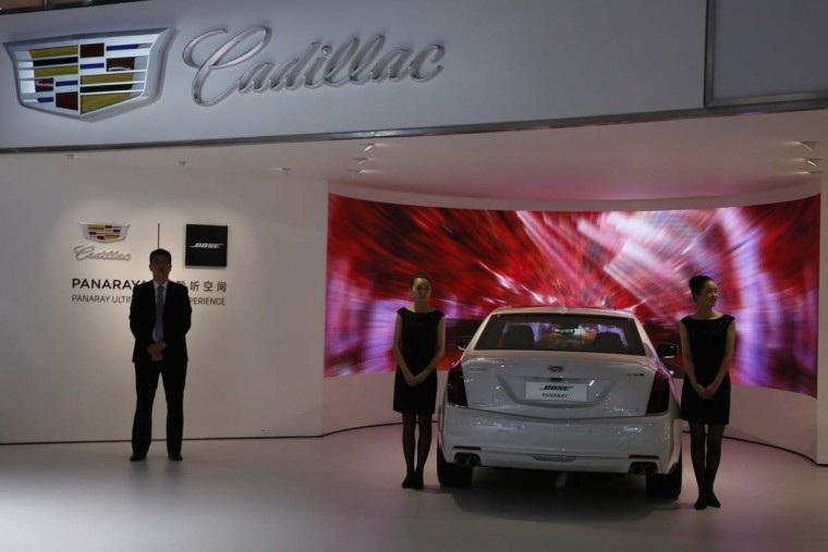 Workers wait at the Cadillac stand during the Auto Shanghai 2017 show at the National Exhibition and Convention Center in Shanghai, China, Wednesday, April 19, 2017. Models on display at Auto Shanghai 2017, the global industry's biggest marketing event of the year, reflect the conflict between Beijing's ambitions to promote environmentally friendly propulsion and Chinese consumers' love of hulking, fuel-hungry SUVs. (AP Photo/Ng Han Guan)