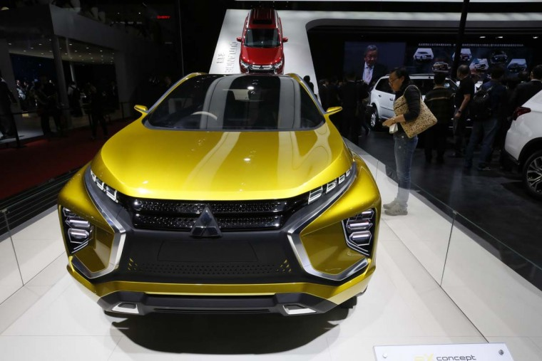 A visitor looks at a concept car from Mitsubishi during the Auto Shanghai 2017 show at the National Exhibition and Convention Center in Shanghai, China, Wednesday, April 19, 2017. Models on display at Auto Shanghai 2017, the global industry's biggest marketing event of the year, reflect the conflict between Beijing's ambitions to promote environmentally friendly propulsion and Chinese consumers' love of hulking, fuel-hungry SUVs. (AP Photo/Ng Han Guan)
