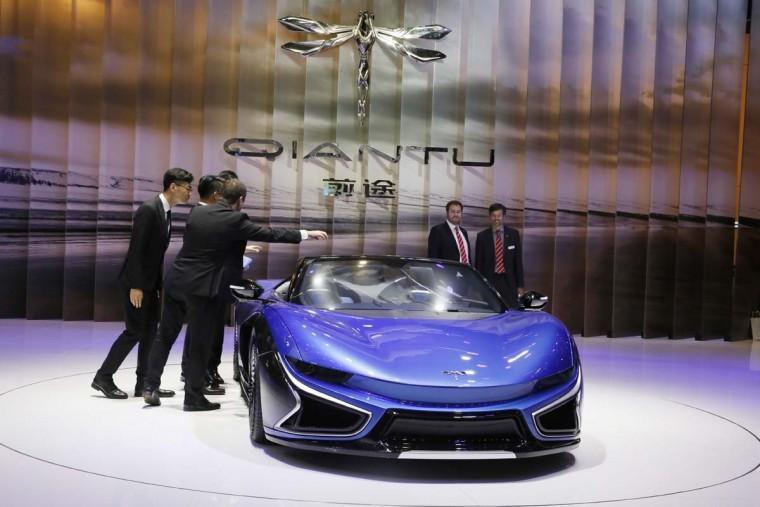 Visitors look at the latest electric sports car from Chinese carmaker Qiantu displayed at the Auto Shanghai 2017 show at the National Exhibition and Convention Center in Shanghai, China, Wednesday, April 19, 2017. Models on display at the Auto Shanghai 2017, the global industry's biggest marketing event of the year, reflect the conflict between Beijing's ambitions to promote environmentally friendly propulsion and Chinese consumers' love of hulking, fuel-hungry SUVs. (AP Photo/Ng Han Guan)
