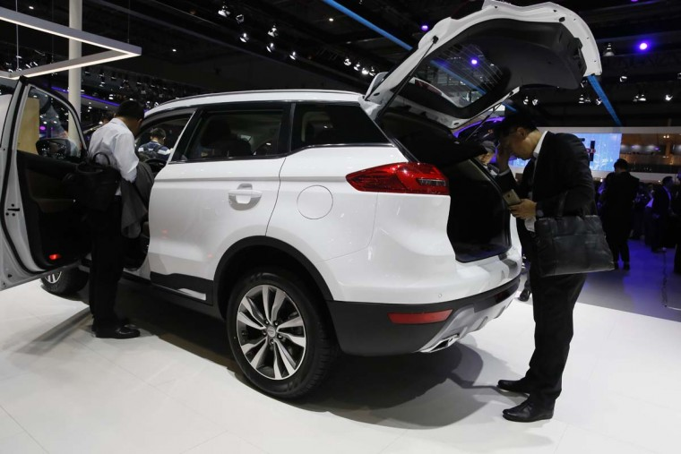 A visitor looks at a SUV from Chinese automaker Geely during the Auto Shanghai 2017 show at the National Exhibition and Convention Center in Shanghai, China, Wednesday, April 19, 2017. Models on display at Auto Shanghai 2017, the global industry's biggest marketing event of the year, reflect the conflict between Beijing's ambitions to promote environmentally friendly propulsion and Chinese consumers' love of hulking, fuel-hungry SUVs. (AP Photo/Ng Han Guan)