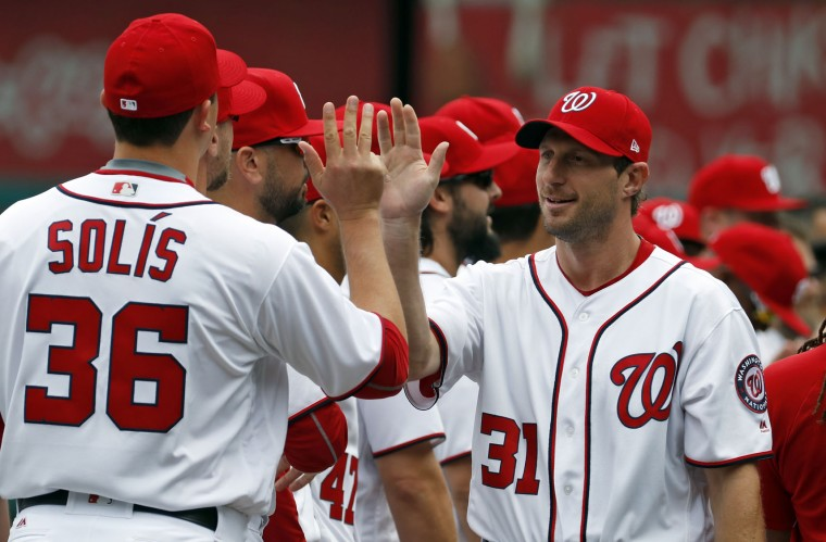 Washington Nationals starting pitcher Max Scherzer (31) greets his teammates during pregame ceremonies before an opening day baseball game against the Miami Marlins, at Nationals Park, Monday, April 3, 2017, in Washington. (AP Photo/Alex Brandon)