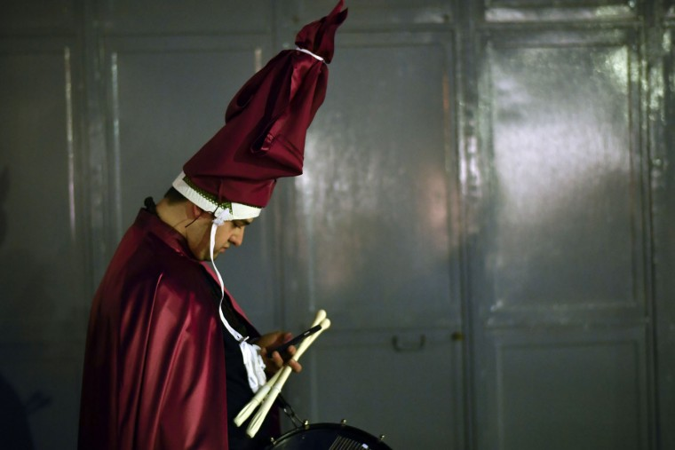 """A penitent checks his personal phone while preparing to takes part in the procession of the """"Santa Veracruz"""" brotherhood, during the Holy Week in Calahorra, northern Spain, Wednesday, April 12, 2017. Hundreds of processions take place throughout Spain during the Easter Holy Week. (AP Photo/Alvaro Barrientos)"""