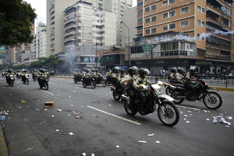 Police officers ride along an avenue during anti-government protests in Caracas, Venezuela, Thursday, April 20, 2017. Tens of thousands of protesters asking for the resignation of President Nicolas Maduro flooded the streets again Thursday, one day after three people were killed and hundreds arrested in the biggest anti-government demonstrations in years. (AP Photo/Ariana Cubillos)