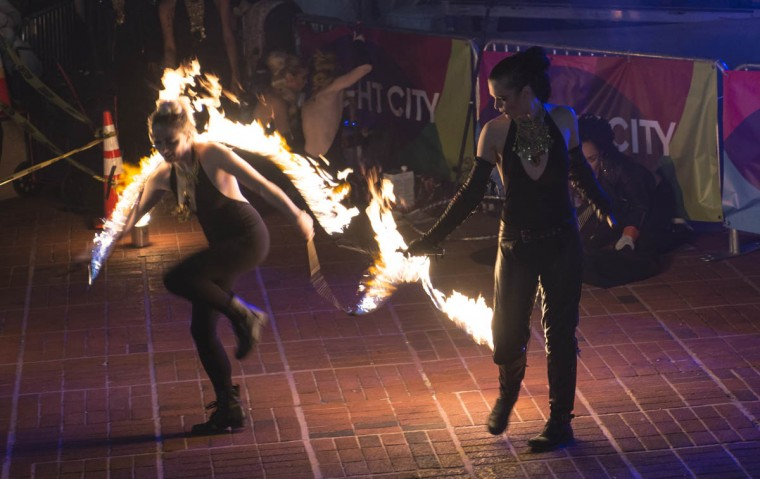 Two performers with PYROXOTIC, an all-female performance troupe, attempt to jump over a rope lit on fire during Light City Baltimore on Wednesday, April 5, 2017. (Emma Harris, Baltimore Sun)