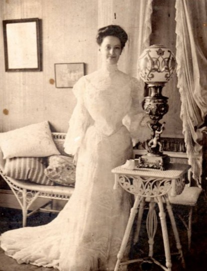 "Black and white image of woman standing in wedding dress in room with lamp and wicker furniture. Back states: ""(1878-1960) Marion Humes/in her wedding dress when she married Philip Calden Turn (1878-1952)."" Matted in gray cardboard. Gift of Mrs. George M. Clarke. (Photo from the Baltimore Historical Society via Enoch Pratt Library)"