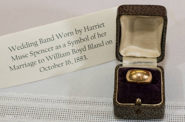 "Gold wedding band, inscribed: ""Semper te amaba/W.B.B. to H.M.G./Oct. 16th 1883."" Sits in small box covered with gray speckled leather and white satin inside lid and purple velvet for ring; metal clasp. Worn by donor's mother, Harriet Muse Spencer, to symbolize her marriage to William Boyd Bland. Gift of Willette Bland. (Photo from the Baltimore Historical Society via Enoch Pratt Library)"