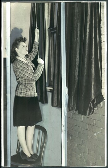 Idoline Jones opens blackout curtains at the Baltimore Sun building in 1942.