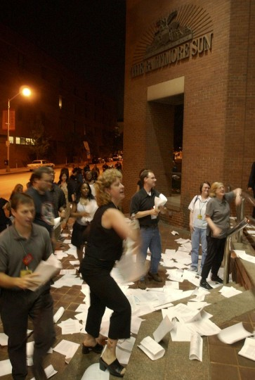Members of the Washington-Baltimore Newspaper Guild toss copies of their new contract on the steps of the The Baltimore Sun building after voting to accept The Sun's contract proposal late Tuesday night, June 24, 2003, in Baltimore, avoiding a possible strike. The vote was 319-102 in favor of accepting the four-year contract, according to the guild. The guild and Sun representatives negotiated for eight weeks on a contract to replace the current agreement, which was to expire at midnight Tuesday. (APPhoto/Gail Burton)