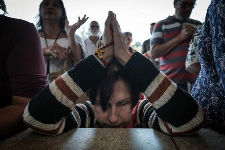 Worshipers in Brazil pray during the centenary Mass marking the apparition of the Virgin Mary at Fatima. (YASUYOSHI CHIBA/AFP/Getty Images)