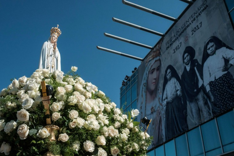 In Brazil, the statue of Our Lady of Fatima is carried by Brazilian Navy personnel past a poster of the child shepherds who reported the apparition of the Virgin Mary. (YASUYOSHI CHIBA/AFP/Getty Images)