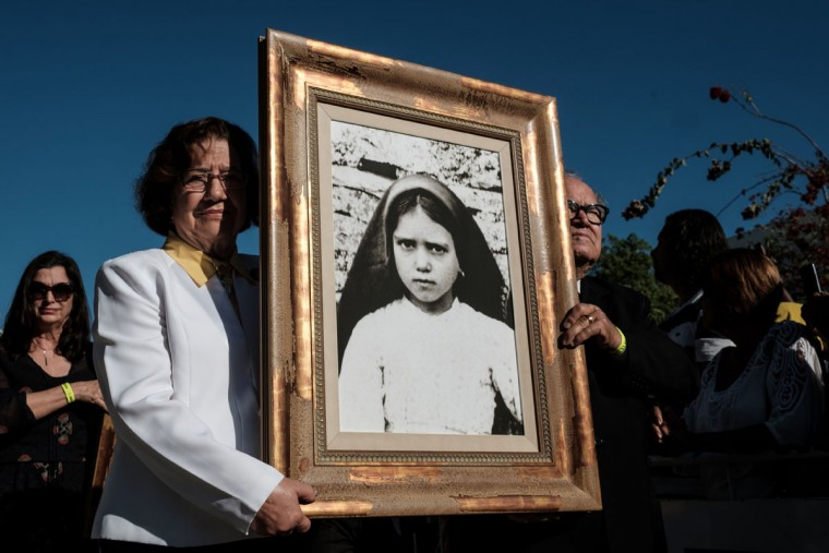 A portrait of child shepherd Jacinta Marto is carried during a centenary Mass in Brazil marking the apparition of the Virgin Mary at Fatima. (YASUYOSHI CHIBA/AFP/Getty Images)