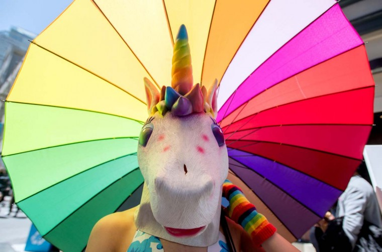 A woman dressed as a unicorn holds a rainbow umbrella at the 18th annual How Weird Street Faire in San Francisco, California on May 07, 2017. Several city blocks filled with thousands of people as they partied and danced in costume to electronic music and interacted with street performers and artists. (JOSH EDELSON/AFP/Getty Images)