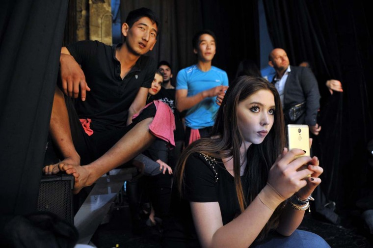 "Participants watch a performance from the backstage area during the ""Kyrgyzstan Pole Sport Championship 2017"" competition in Bishkek late on May 1, 2017. (VYACHESLAV OSELEDKO/AFP/Getty Images)"