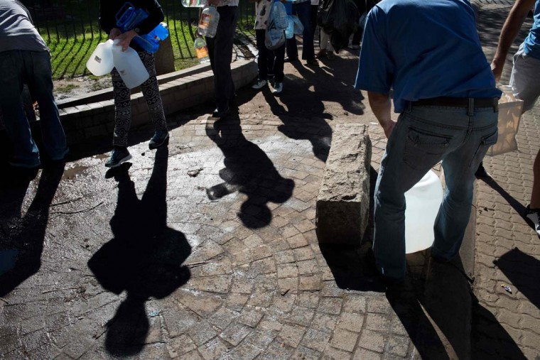 People queue up to collect drinking water from taps that are fed by a spring in Newlands on May 15, 2017, in Cape Town. South Africa's Western Cape region which includes Cape Town declared a drought disaster on May 22 as the province battled its worst water shortages for 113 years. This dam is the main water source for the city of Cape Town, and there is only 10% of it's usual capacity left for human consumption, at the last 10% is not usable, due to the silt content. (RODGER BOSCH/AFP/Getty Images)