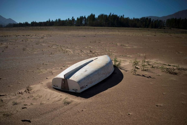 A picture taken on May 10, 2017 shows a boat lying on the sand at the Theewaterskloof Dam, which has less than 20% of it's water capacity, near Villiersdorp, about 108 km from Cape Town. This dam is the main water source for the city of Cape Town, and there is only 10% of it's usual capacity left for human consumption, at the last 10% is not usable, due to the silt content. The Western Cape Province, which includes Cape Town is suffering from one of the worst water shortages in living memory. This has necessitated the Cape Town City Council to establish stringent water usage restrictions, and unless unexpectedly heavy rains fall soon, the province will begin a cycle of drought. (RODGER BOSCH/AFP/Getty Images)
