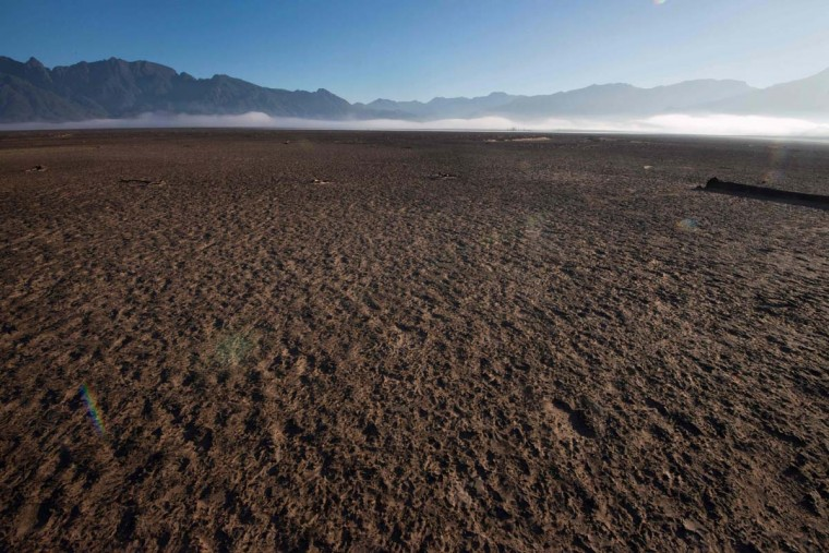 A picture taken on May 10, 2017 shows bare sand exposed to the sky at Theewaterskloof Dam, which has less than 20% of it's water capacity, near Villiersdorp, about 108 km from Cape Town. South Africa's Western Cape region which includes Cape Town declared a drought disaster on May 22 as the province battled its worst water shortages for 113 years. This dam is the main water source for the city of Cape Town, and there is only 10% of it's usual capacity left for human consumption, at the last 10% is not usable, due to the silt content. (RODGER BOSCH/AFP/Getty Images)