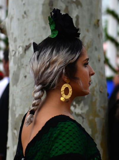 "A woman wearing a traditional Sevillian dress looks on during the ""Feria de Abril"" (April Fair) in Sevilla on April 30, 2017. The fair dates back to 1847 when it was originally organized as a livestock fair but has turned into a week of flamenco dancing, music and bullfighting. (Cristina Quicler/AFP/Getty Images)"