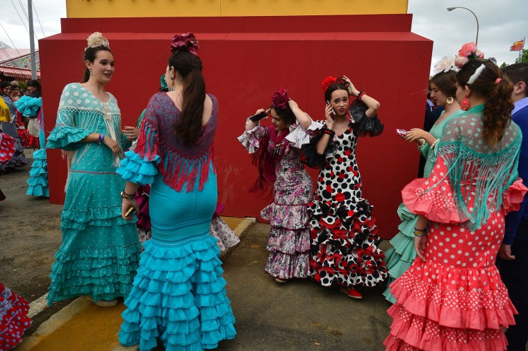 "Girls wearing traditional Sevillian dresses gather during the ""Feria de Abril"" (April Fair) in Sevilla on April 30, 2017. The fair dates back to 1847 when it was originally organized as a livestock fair but has turned into a week of flamenco dancing, music and bullfighting. (Cristina Quicler/AFP/Getty Images)"