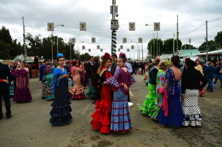 "Girls wearing traditional Sevillian dresses look on during the ""Feria de Abril"" (April Fair) in Sevilla on April 30, 2017. The fair dates back to 1847 when it was originally organized as a livestock fair but has turned into a week of flamenco dancing, music and bullfighting. (Cristina Quicler/AFP/Getty Images)"