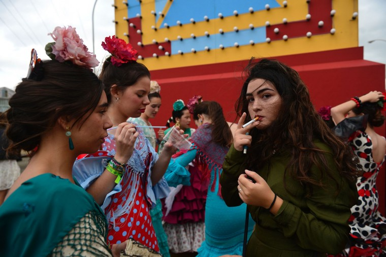 "A girl smokes a cigarrette beside others wearing traditional Sevillian dresses during the ""Feria de Abril"" (April Fair) in Sevilla on April 30, 2017. The fair dates back to 1847 when it was originally organized as a livestock fair but has turned into a week of flamenco dancing, music and bullfighting. (Cristina Quicler/AFP/Getty Images)"