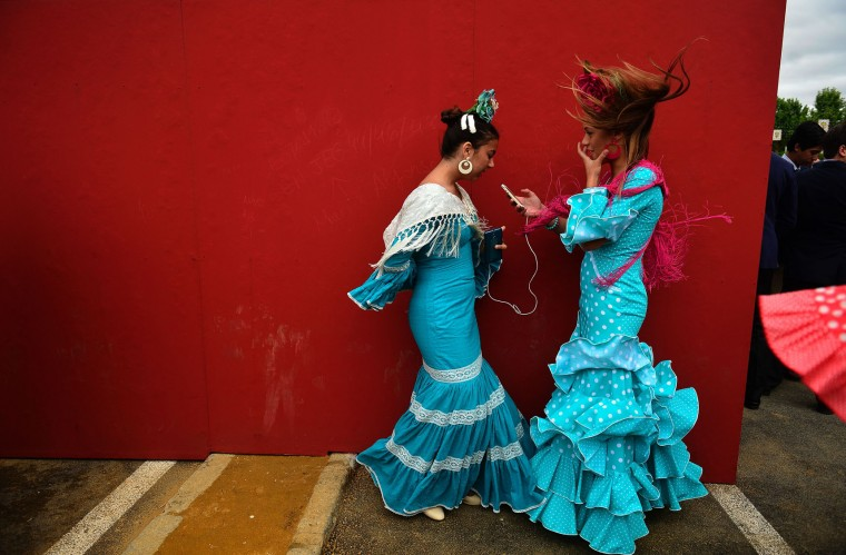 "Two girls wearing traditional Sevillian dresses talk during the ""Feria de Abril"" (April Fair) in Sevilla on April 30, 2017. The fair dates back to 1847 when it was originally organized as a livestock fair but has turned into a week of flamenco dancing, music and bullfighting. (Cristina Quicler/AFP/Getty Images)"
