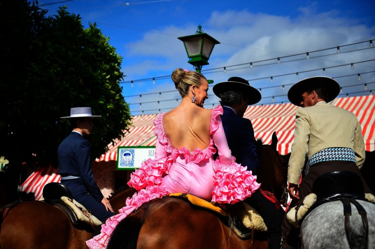 "A woman wearing a traditional Sevillian dress sits on a horse during the ""Feria de Abril"" (April Fair) in Sevilla on April 30, 2017. The fair dates back to 1847 when it was originally organized as a livestock fair but has turned into a week of flamenco dancing, music and bullfighting. (Cristina Quicler/AFP/Getty Images)"