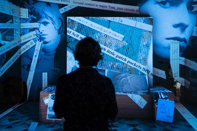 "A visitor looks at an installation art wtih images representing British pop icon David Bowie during the exhibition ""David Bowie is"" at the Museum of the Design of Barcelona, on May 24, 2017. (Josep Lago/AFP/Getty Images)"