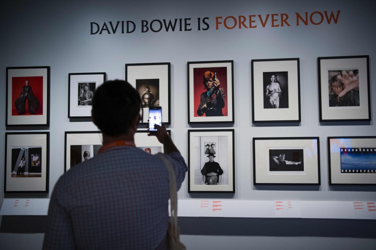 "A man photographs pictures of US artist David Bowie during the exhibition ""David Bowie is"" at the Museum of the Design of Barcelona, on May 24, 2017. (Josep Lago/AFP/Getty Images)"