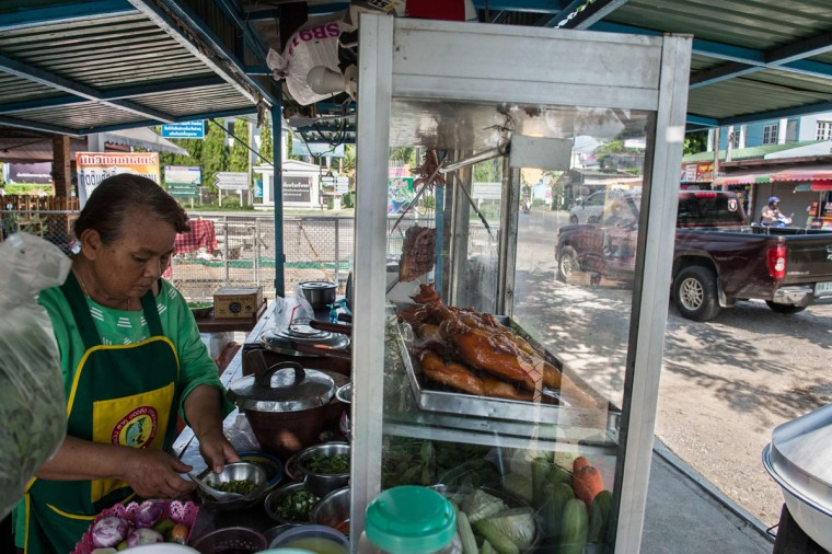 This picture taken on May 4, 2017 shows Mali Pansari, the wife of food vendor Sila Sutharat, preparing garnishes as solar-cooked chicken is displayed on their counter at their eatery in Petchaburi province, south of Bangkok. Not many chefs don a welding mask before they enter the kitchen, but Sila Sutharat prefers to cook his chicken sunny side up. Two hours south of Bangkok this 60-year-old vendor has found an ingenious way to offer his customers something a little different by harnessing the power of the sun. Using a large wall of nearly 1,000 moveable mirrors -- a device he designed and built himself -- he focuses the sun's rays onto a row of marinated chickens, sizzling away under the intense heat. (ROBERTO SCHMIDT/AFP/Getty Images)