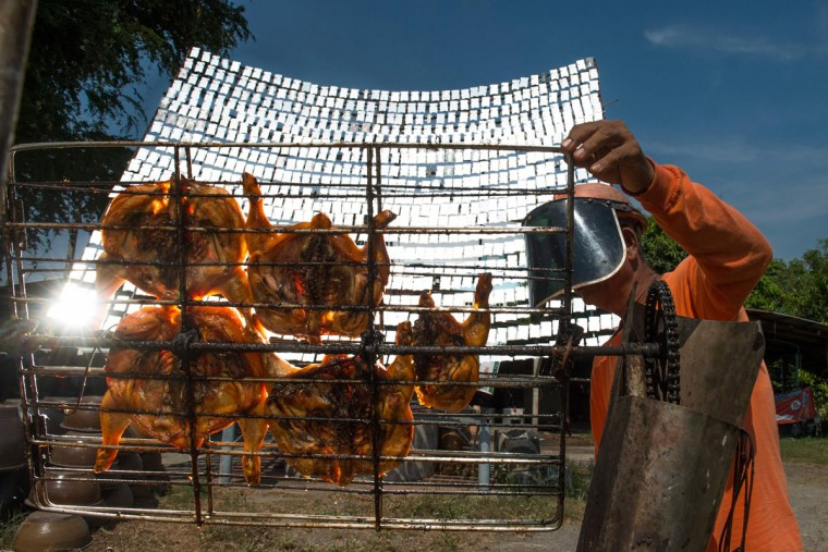 This picture taken on May 4, 2017 shows food vendor Sila Sutharat turning the grates on a cart loaded with chicken as he cooks the white meat with rays of sun reflected on an oversized mirror panel on his property in Petchaburi province, south of Bangkok. Not many chefs don a welding mask before they enter the kitchen, but Sila Sutharat prefers to cook his chicken sunny side up. Two hours south of Bangkok this 60-year-old vendor has found an ingenious way to offer his customers something a little different by harnessing the power of the sun. Using a large wall of nearly 1,000 moveable mirrors -- a device he designed and built himself -- he focuses the sun's rays onto a row of marinated chickens, sizzling away under the intense heat. (ROBERTO SCHMIDT/AFP/Getty Images)