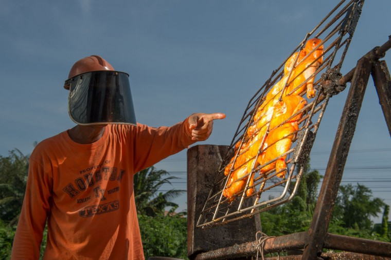 This picture taken on May 4, 2017 shows food vendor Sila Sutharat pointing to chickens being cooked by rays of sun reflected onto an oversized mirror panel on his property in Petchaburi province, south of Bangkok. Not many chefs don a welding mask before they enter the kitchen, but Sila Sutharat prefers to cook his chicken sunny side up. Two hours south of Bangkok this 60-year-old vendor has found an ingenious way to offer his customers something a little different by harnessing the power of the sun. Using a large wall of nearly 1,000 moveable mirrors -- a device he designed and built himself -- he focuses the sun's rays onto a row of marinated chickens, sizzling away under the intense heat. (ROBERTO SCHMIDT/AFP/Getty Images)