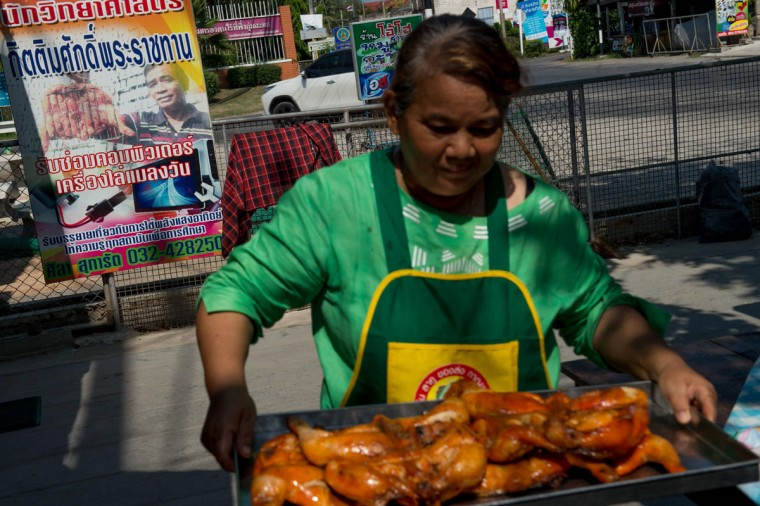 This picture taken on May 4, 2017 shows Mali Pansari, the wife of food vendor food vendor Sila Sutharat, carrying a tray of cooked chicken past an advertising panel displaying the photo of her husband at their eatery in Petchaburi province, south of Bangkok. Not many chefs don a welding mask before they enter the kitchen, but Sila Sutharat prefers to cook his chicken sunny side up. Two hours south of Bangkok this 60-year-old vendor has found an ingenious way to offer his customers something a little different by harnessing the power of the sun. Using a large wall of nearly 1,000 moveable mirrors -- a device he designed and built himself -- he focuses the sun's rays onto a row of marinated chickens, sizzling away under the intense heat. (ROBERTO SCHMIDT/AFP/Getty Images)