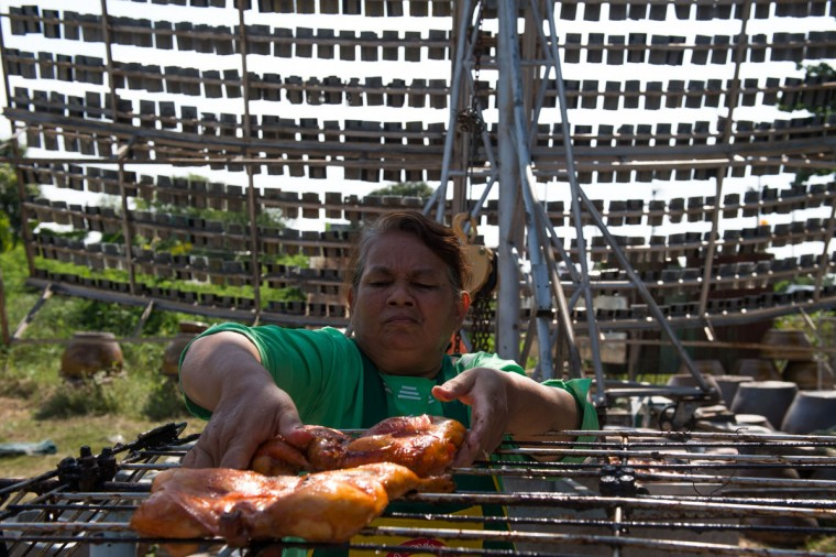 This picture taken on May 4, 2017 shows Mali Pansari, the wife of food vendor Sila Sutharat, removing chicken from the grill after they were cooked with rays of the sun reflected on an over-sized mirror panel (background) on their property in Petchaburi province, south of Bangkok. Not many chefs don a welding mask before they enter the kitchen, but Sila Sutharat prefers to cook his chicken sunny side up. Two hours south of Bangkok this 60-year-old vendor has found an ingenious way to offer his customers something a little different by harnessing the power of the sun. Using a large wall of nearly 1,000 moveable mirrors -- a device he designed and built himself -- he focuses the sun's rays onto a row of marinated chickens, sizzling away under the intense heat. (ROBERTO SCHMIDT/AFP/Getty Images)