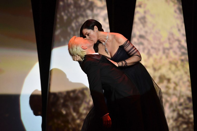 Italian actress and master of ceremonies Monica Bellucci (R) and French comedian Alex Lutz kiss as they perform on stage on May 17, 2017 during of the opening ceremony of the 70th edition of the Cannes Film Festival in Cannes, southern France. (Alberto Pizzoli/AFP/Getty Images)