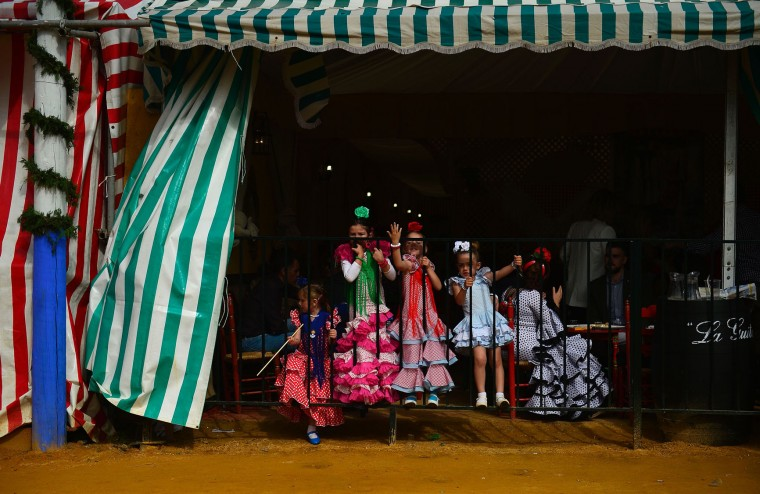 "Little girls wearing traditional Sevillian dresses play during the ""Feria de Abril"" (April Fair) in Sevilla on April 30, 2017. The fair dates back to 1847 when it was originally organized as a livestock fair but has turned into a week of flamenco dancing, music and bullfighting. (Cristina Quicler/AFP/Getty Images)"