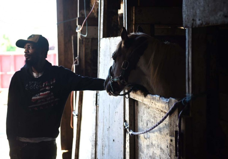 Jamil Prettis stands with a horse at the Fletcher Street Urban Riding Club in North Philadelphia on May 16, 2017. The club, a non-profit organization devoted to inner-city horsemanship in north Philadelphia, has used the century-long tradition of black urban cowboys and horsemanship in Philadelphia as a way to keep kids out of trouble by teaching them riding and caring for horses. (TIMOTHY A. CLARY/AFP/Getty Images)