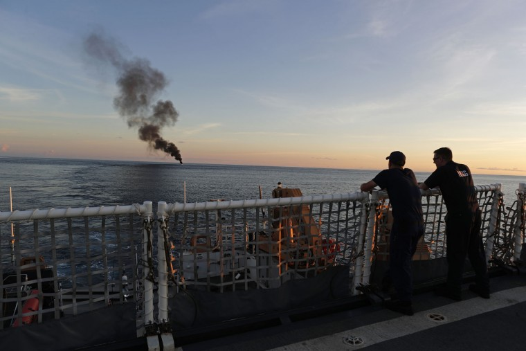 In this Feb. 23, 2017 photo, two Coast Guardsmen watch from the U.S. Coast Guard cutter Stratton as a small fishing boat was set ablaze by the Coast Guard after close to 700 kilograms of cocaine were seized and four men were detained, in the Pacific Ocean, hundreds of miles south of the Guatemala-El Salvador border. A few hours later, the Stratton fired its cannon and sank the boat.(AP Photo/Dario Lopez-Mills)