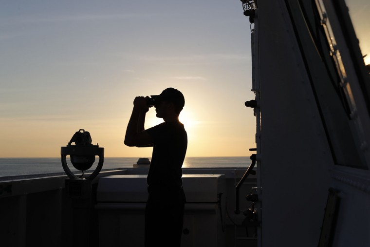 In this Feb. 22, 2017 photo, a U.S. Coast Guard sailor scans the horizon with his binoculars just outside the bridge of the USCG cutter Stratton as it navigates the eastern Pacific Ocean near the coast of Central America. The Coast Guard set a record in 2016, seizing more than 240 tons of cocaine, but its victories seem doomed to be short-lived. That's because hundreds of miles to the south, in the jungles of Colombia, there's a bumper harvest taking place. And Colombia is virtually the only source of cocaine smuggled by sea in small vessels.(AP Photo/Dario Lopez-Mills)