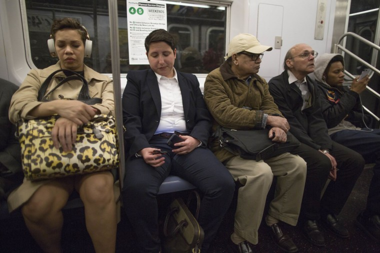 In this Wednesday, May 10, 2017, photo, attorney Kim Juszczak, second from left, uses a fidget spinner while riding the subway in New York. Fidget spinners have been around for years, mostly used by kids with autism or attention disorders to help them concentrate. But they exploded in popularity this spring. Juszczak likes to whirl her spinner on the subway or while she's thinking up legal arguments for a case. (AP Photo/Mary Altaffer)