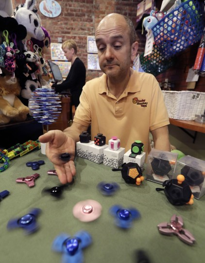 "In this Thursday, May 11, 2017, photo, Funky Monkey Toys store owner Tom Jones plays with some fidget spinners he sells, in Oxford, Mich. Stores can't keep them in stock and parents are going crazy trying to find them. ""We run out of them frequently,"" says Jones, who recently got a shipment of 2,000. (AP Photo/Carlos Osorio)"