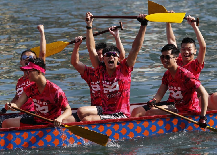 Participants celebrate winning a dragon boat race in Hong Kong Tuesday, May 30, 2017, as part of celebrations marking the Chinese Dragon Boat Festival, held throughout the islands. (AP Photo/Vincent Yu)
