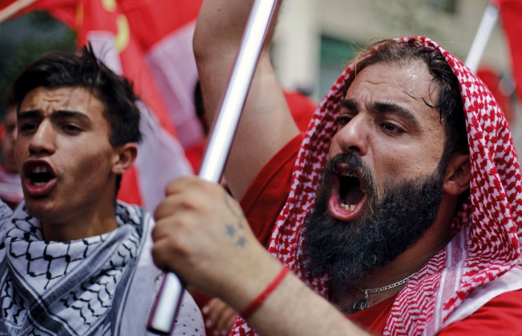 Members and supporters of the Lebanese Communist party, chant pro-worker slogans and wave Lebanese flags with Communist symbols, during a demonstration to mark International Labor Day or May Day, in Beirut, Lebanon, Monday, May 1, 2017. Workers and activists marked May Day around the world Monday with defiant rallies and marches for better pay and working conditions. (AP Photo/Bilal Hussein)
