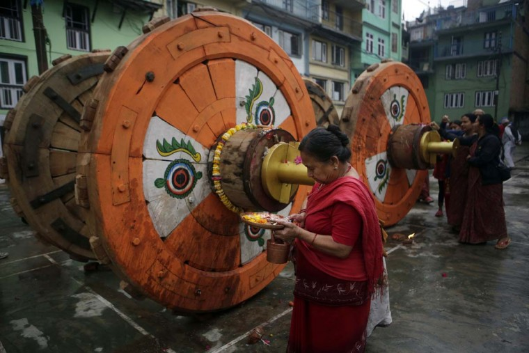 In this April 21, 2017, photo, a Hindu woman performs ritual prayers in front of wheels that will be assembled for the Rato Machindranath Chariot in Lalitpur, Nepal. The chariot built every year is 15-meter (48-foot) tall and based on a chassis that is only as wide as a small truck. The chariot rides high over the heads of people as it sits on four giant wooden wheels decorated with painted eyes. The wooden chariot is built to appease the gods in hopes of being blessed with a good rainfall followed by a bountiful harvest. (AP Photo/Niranjan Shrestha)