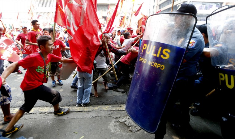 "Protesters clash with riot police as they attempt to force their way closer to U.S. Embassy to mark May Day celebrations in Manila, Philippines, Monday, May 1, 2017. As in the past years, workers mark Labor Day with calls for higher wages and an end to the so-called ""Endo"" or contractualization. (AP Photo/Bullit Marquez)"