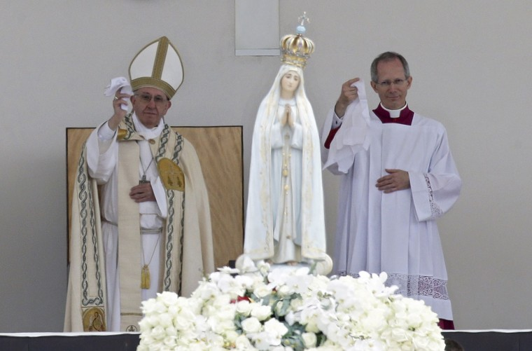 Pope Francis, left, and Master of Pontifical Liturgical Celebrations Guido Marini wave white handkerchiefs as the statue of Our Lady of Fatima is carried at the end of the canonization Mass. (AP Photo/Armando Franca)