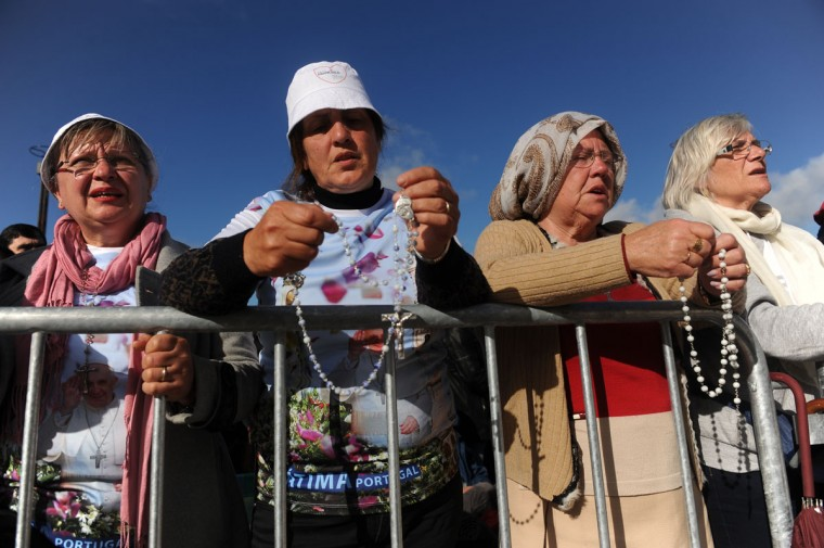 Pilgrims and faithful wait for the start of the Mass where Pope Francis canonized Jacinta and Francisco Marto at the Sanctuary of Our Lady of Fatima in Fatima, Portugal. (AP Photo/Paulo Duarte)