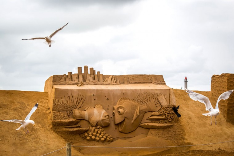 Seagulls fly next to sand sculptures representing characters and scenes of Disney movies during an exhibition Disney Sand Magic in Ostende, on June 29, 2017. (AFP Photo/ Aurore Belot)