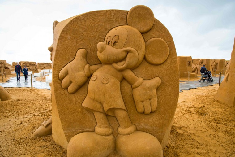 People walk past sand sculptures representing characters and scenes of Disney movies during an exhibition Disney Sand Magic in Ostende, on June 29, 2017. (AFP Photo/ Aurore Belot)
