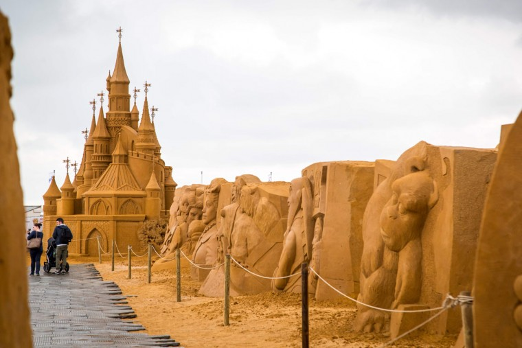 People stand next to sand sculptures representing characters and scenes of Disney movies during an exhibition Disney Sand Magic in Ostende, on June 29, 2017. (AFP Photo/ Aurore Belot)